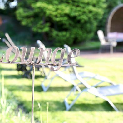 """Schild """"Lounge"""" im Garten auf der Wiese"""