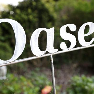 """Schild """"Oase"""" im Garten"""